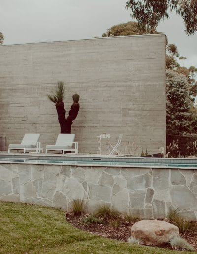 Photo of pool area with white wall, crazy paving and sun lounges