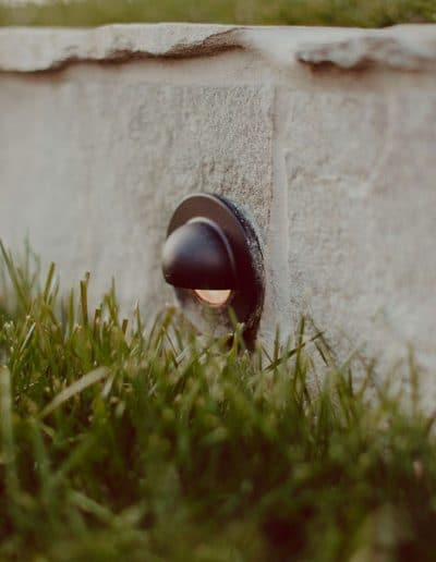 Closeup photo of garden light in pale stone retaining wall