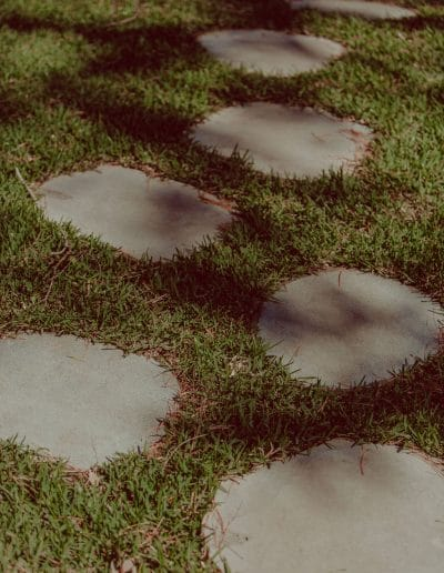 Closeup of rounded stone pavers set in lawn